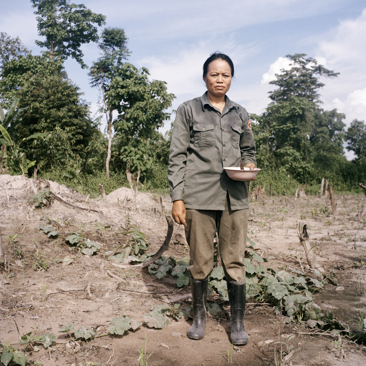 Mank works in her farmland in Dongphosy village. When construction for the track begins, she and her family will be displaced.