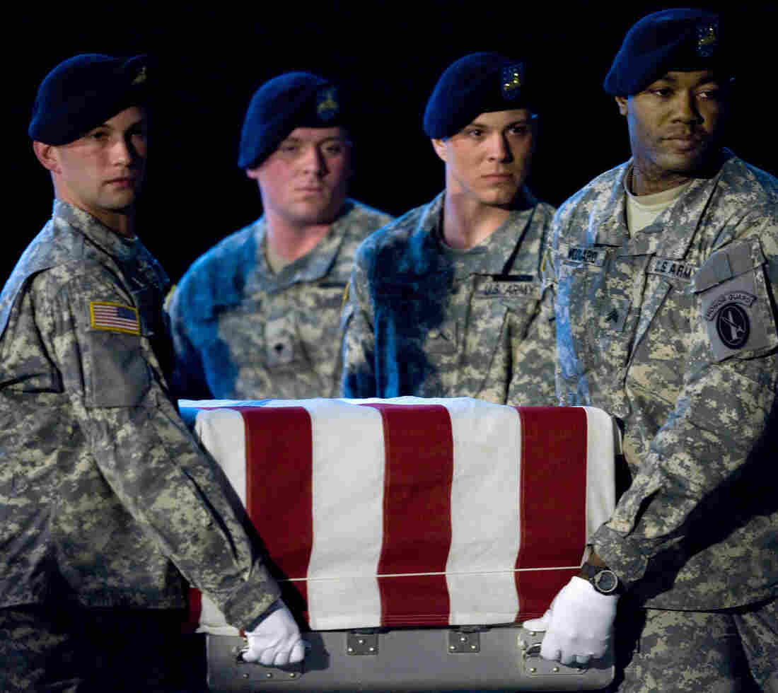 Members of the US Army's Old Guard carry team lift the remains of U.S. Army Specialist Israel Candelaria Mejias from San Lorenzo, Puerto Rico, as his body is returned on a C-17 to the U.S. from Iraq on April 7, 2009.