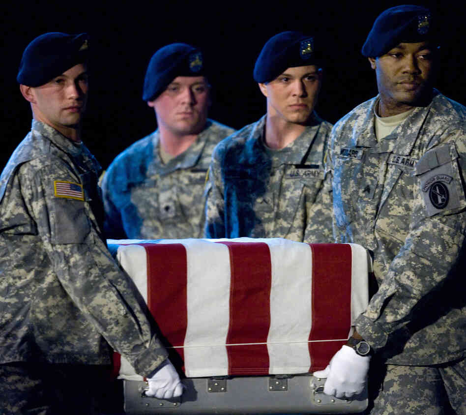 Members of the US Army's Old Guard carry team lift the remains of U.S. Army Specialist Israel Candelaria Mejias from San Lorenzo,