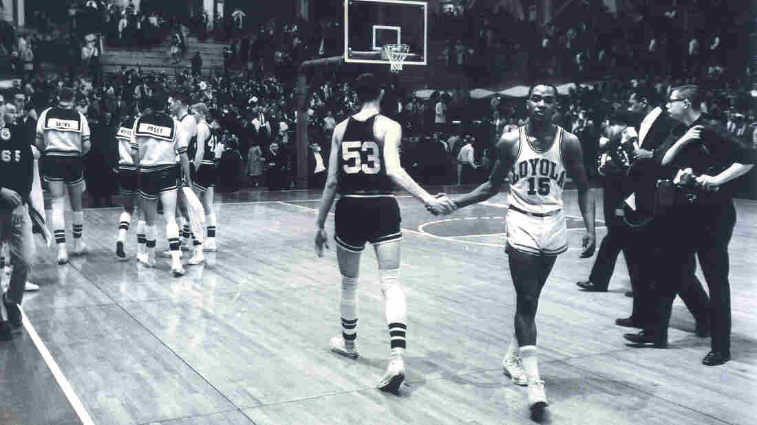 Mississippi State's Stan Brinker (53) and Loyola's Jerry Harkness (15) shake hands before the NCAA Mideast regional semifinal college basketball game in East Lansing, Mich., on March 15, 1963. The game was a landmark contest between the schools that helped alter race relations on the basketball court.