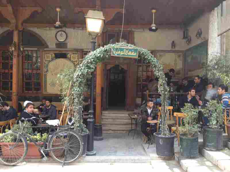 Members of the government security forces relax at a cafe. Daily life carries on in Damascus two years after the uprising began.