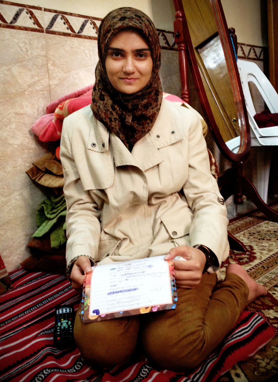 Guffran, 16, sits on the floor of her home, holding a letter she wrote to her father. A Shiite Muslim, Guffran's father was gunned down on the streets of Baghdad in 2006.