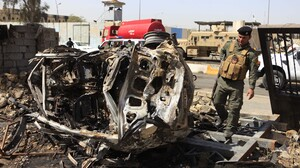 An Iraqi soldier stands at the scene of a car bomb attack on the Justice Ministry a day earlier, in Baghdad on Friday.