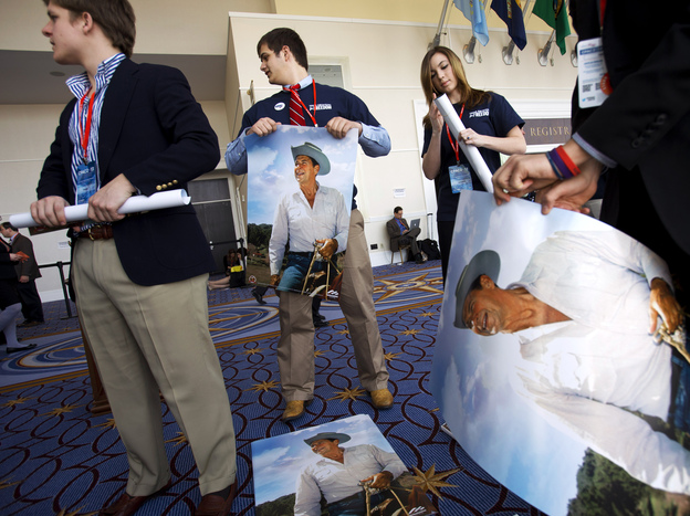 Members of the college group Young Americans for Freedom roll up Ronald Reagan posters to hand out at CPAC in National Harbor, Md. on Friday.
