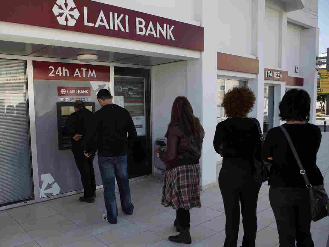 People queue to use an ATM outside of a Laiki Bank branch in Larnaca, Cyprus, on Saturday. Many rushed to cooperative banks after learning that the terms of a bailout deal with international lenders includes a one-time levy on bank deposits.
