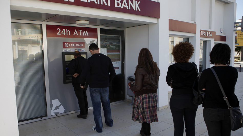 People queue to use an ATM outside of a Laiki Bank branch in Larnaca, Cyprus, on Saturday. Many rushed to cooperative banks after learning that the terms of a bailout deal with international lenders includes a one-time levy on bank deposits. (AP)