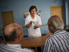 Social worker Nuria Casulleres shows a portrait of Audrey Hepburn to elderly men during a memory activity at the Cuidem La Memoria elderly home in Barcelona, Spain, last August. The home specializes in Alzheimer's patients.