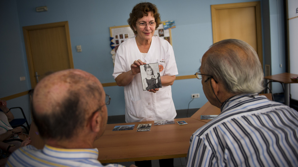 Social worker Nuria Casulleres shows a portrait of Audrey Hepburn to elderly men during a memory activity at the Cuidem La Memoria elderly home in Barcelona, Spain, last August. The home specializes in Alzheimer's patients. (Getty Images)
