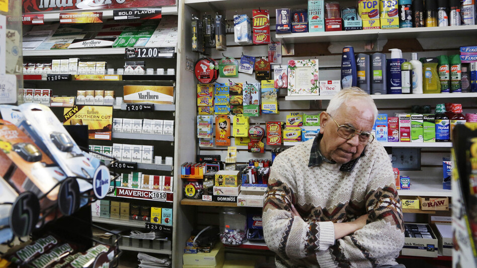Harry Patel, an employee of Blondie's Deli and Grocery, talks on the phone while waiting for customers in New York on Monday. A new anti-smoking proposal would make New York the first city in the nation to keep tobacco products out of sight in retail stores. (AP)