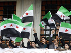 Demonstrators wave Syrian opposition flags during a protest in Istanbul against the government of Syria's President Bashar Assad, on March 15.