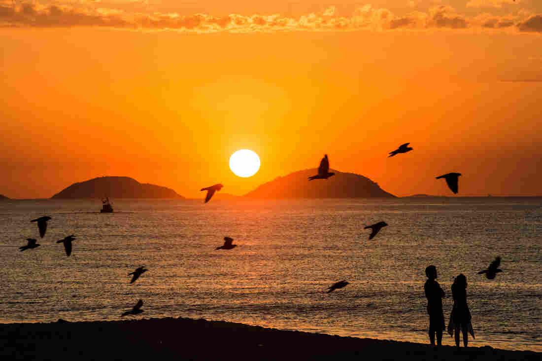 A couple watch the sunrise at Copacabana beach in Rio de Janeiro, Brazil, on Februrary 26, 2013.