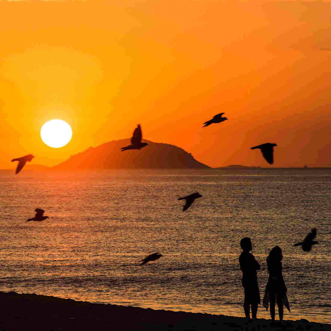 A couple watch the sunrise at Copacabana beach in Rio de Janeiro, Brazil, on Februrary 26, 2013.