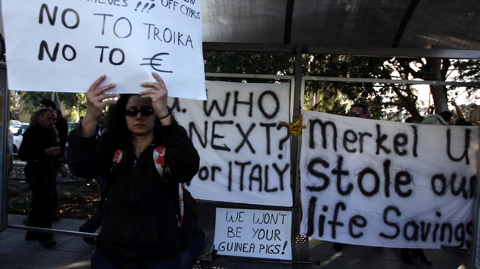 A Cypriot woman holds a sign during a protest against an EU bailout deal outside the Parliament in Nicosia on Monday.