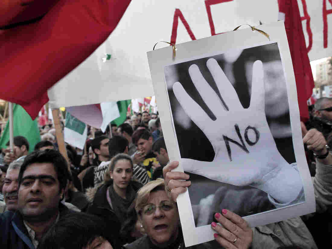 Protesters chant slogans outside the Cypriot parliament in central Nicosia, Tuesday, March 19, 2013.