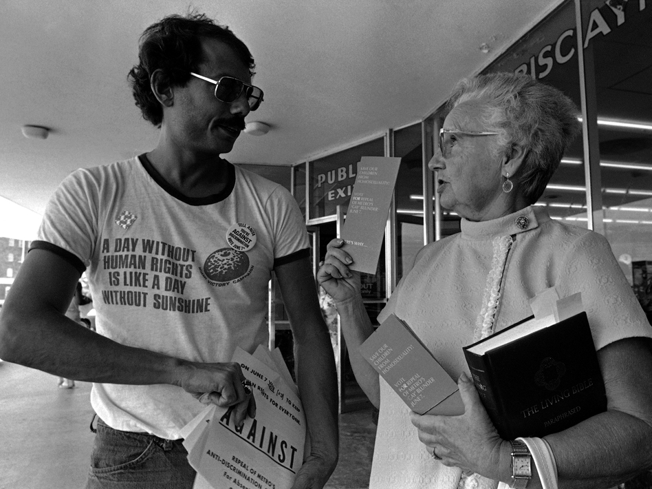 Doris Dennis, a volunteer handing out literature for the Save Our Children group headed by Anita Bryant, gets into a debate with Alan Rockway, a volunteer handing out literature for a gay rights group, at a shopping center in Miami in 1977. (AP)