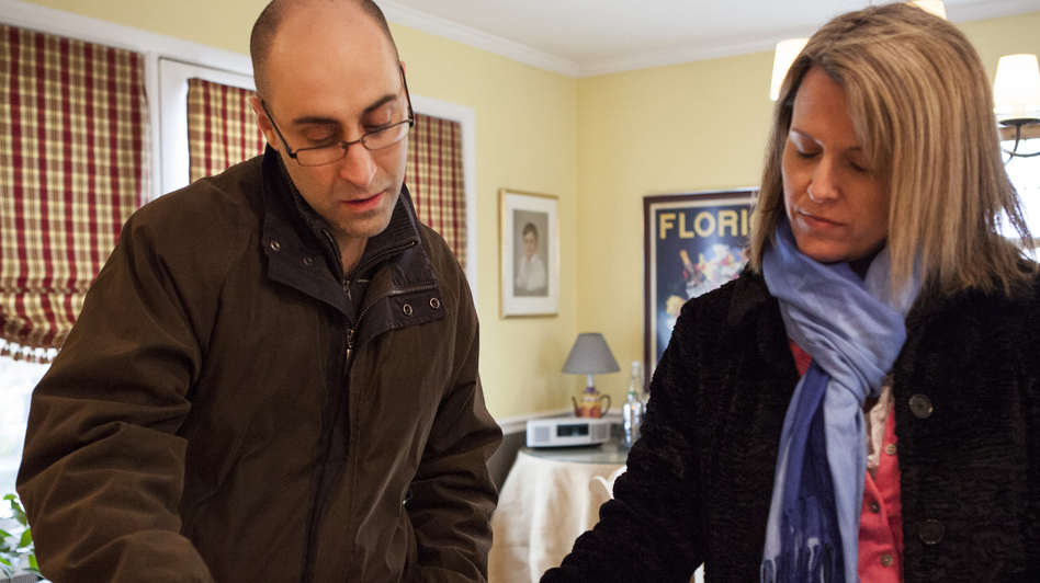 Patrick Bove, a homebuyer (and seller), and Redfin real estate agent Lynn Ikle look at a pamphlet at an open house in Towson, Md. (Lauren Rock for NPR)