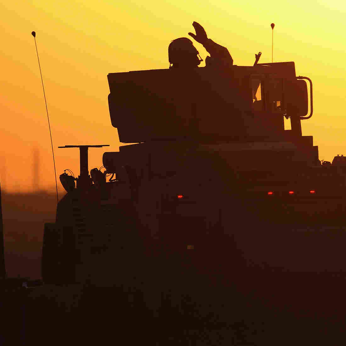 A soldier in the last American military convoy to depart Iraq, from the 3rd Brigade, 1st Cavalry Division, waves after crossing over the border into Kuwait on Dec. 18, 2011.