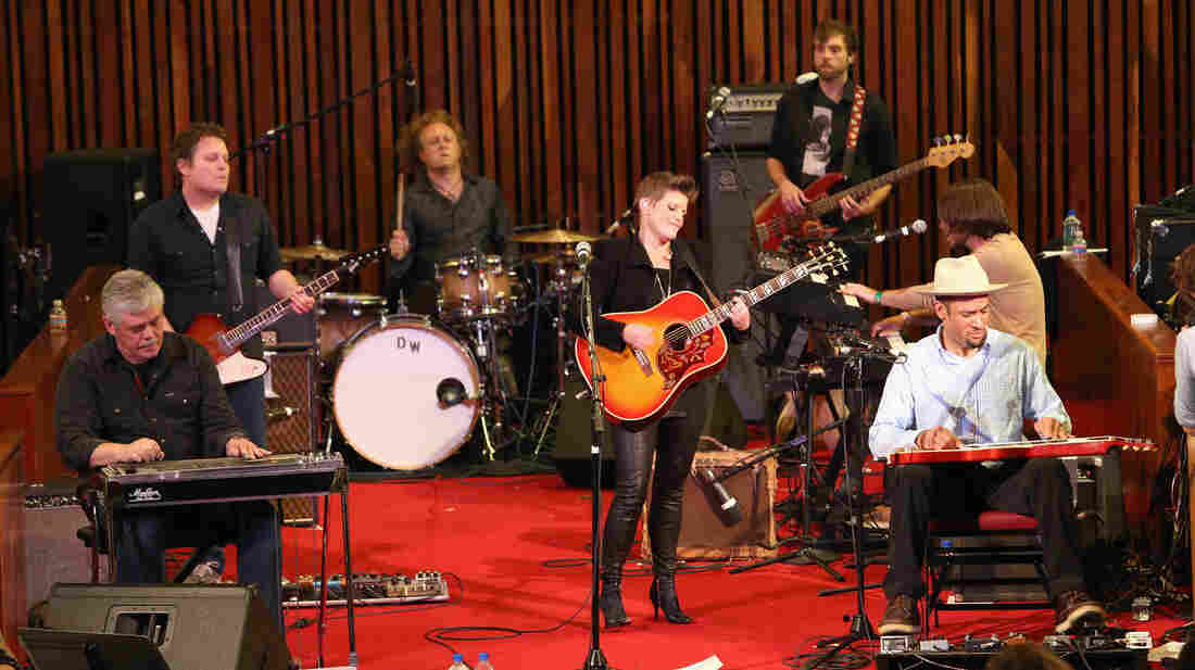 Natalie Maines (center) at Central Presbyterian Church in Austin, Texas during the SXSW Music Festival. Maines's band included her father, Lloyd Maines (seated left) and Ben Harper (seated right).
