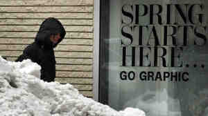 The sign says one thing. The snow pile says another. In Boston on Tuesday, a woman walked between a store sign heralding the start of spring and a snow pile still lingering from this winter's storms.
