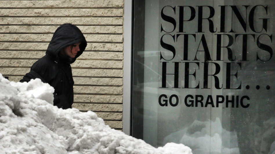 The sign says one thing. The snow pile says another. In Boston on Tuesday, a woman walked between a store sign heralding the start of spring and a snow pile still lingering from this winter's storms. (Reuters /Landov)