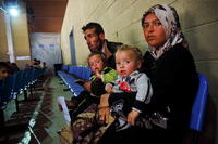 Um Ahmed, her husband, Abu Ahmed, and their two children sit inside a United Nations refugee registration center in Tripoli, Lebanon. They fled the northern Syrian city of Aleppo a month ago.