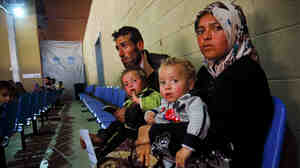 "Um Ahmed, her husband, Abu Ahmed, and their two children sit inside a United Nations refugee registration center in Tripoli, Lebanon. They fled the northern Syrian city of Aleppo a month ago. ""There was a lot of shelling,"" said Um Ahmed. ""I wasn't thinking. I was just thinking of my children."""