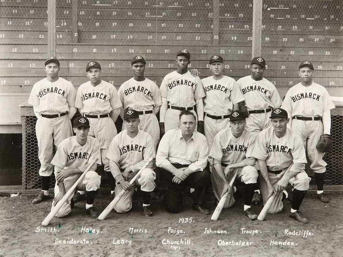 The only known photograph of the 1935 Bismark town team shows manager Neil Churchill, kneeling in the center, and pitcher Satchel Paige standing behind him.