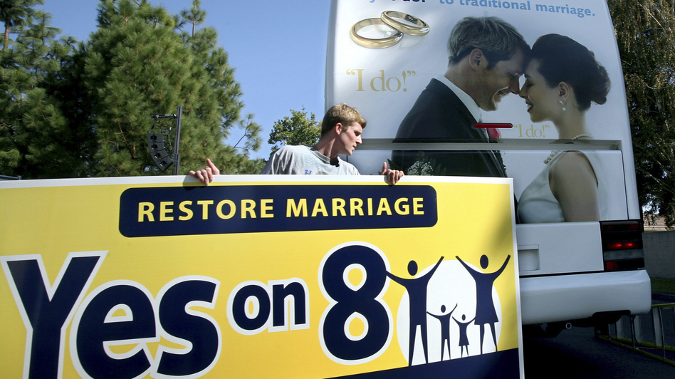 Richie Beanan of Los Angeles puts a sign on a bus in support of California's Proposition 8 gay marriage ban after a rally in Sacramento in October 2008. (AP)