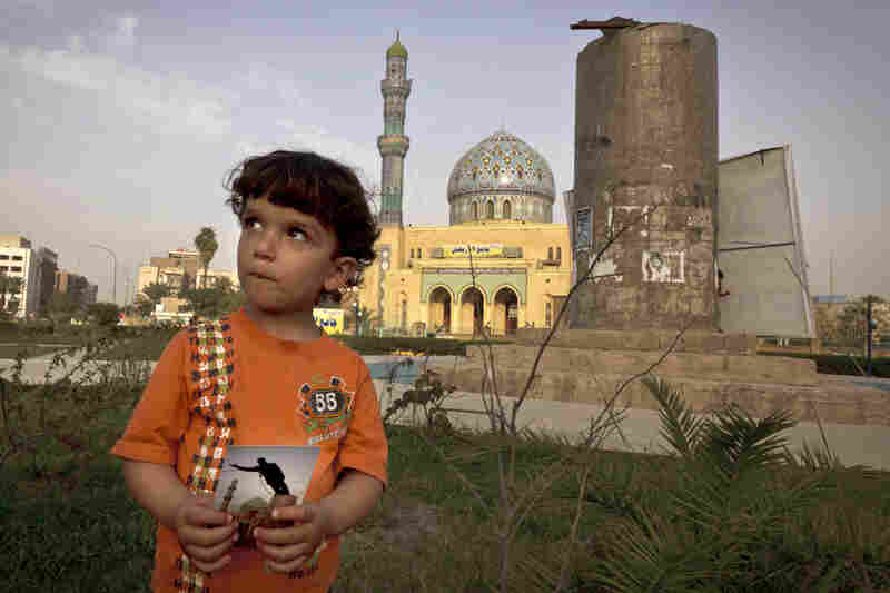 Hussein, 3, poses in Firdous Square in Baghdad with a 2003 photograph taken by Jerome Delay — showing the statue of Saddam Hussein being pulled down by U.S. forces and Iraqis.