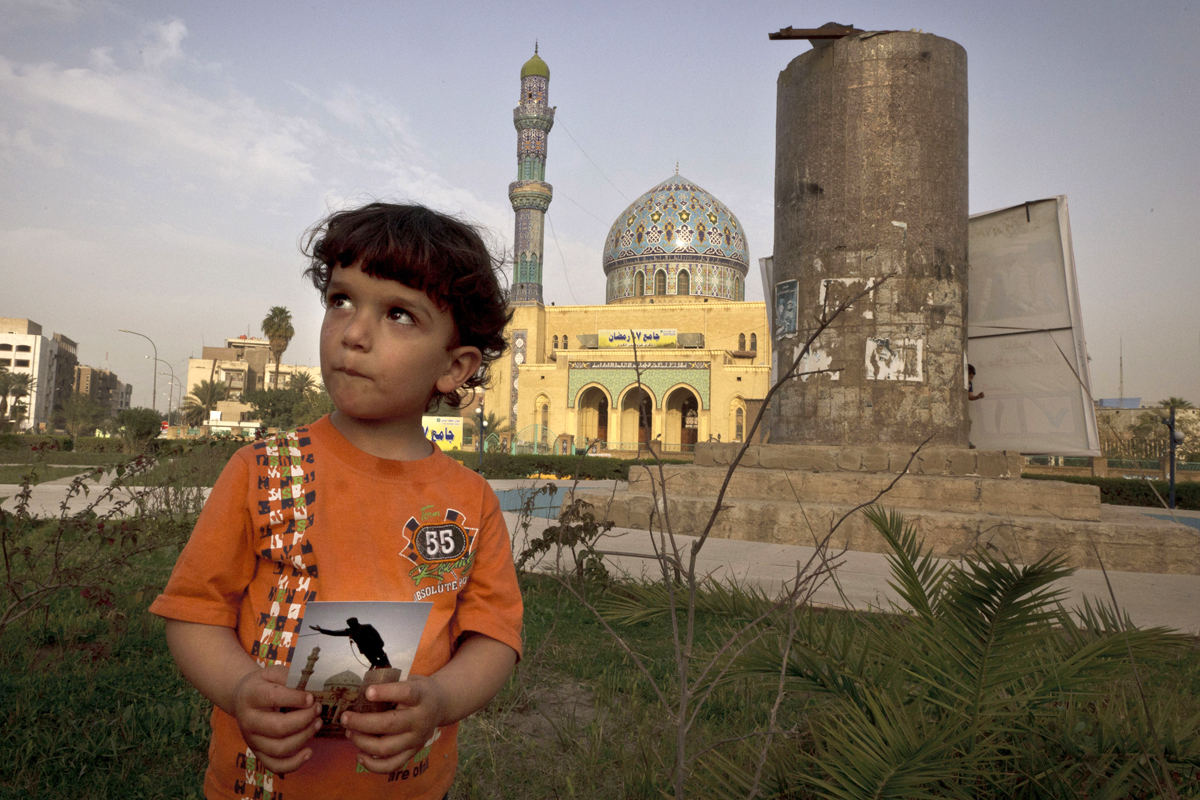 Hussein, 3, poses in Firdous Square in Baghdad with a 2003 photograph taken by Jerome Delay -- showing the statue of Saddam Hussein being pulled down by U.S. forces and Iraqis.