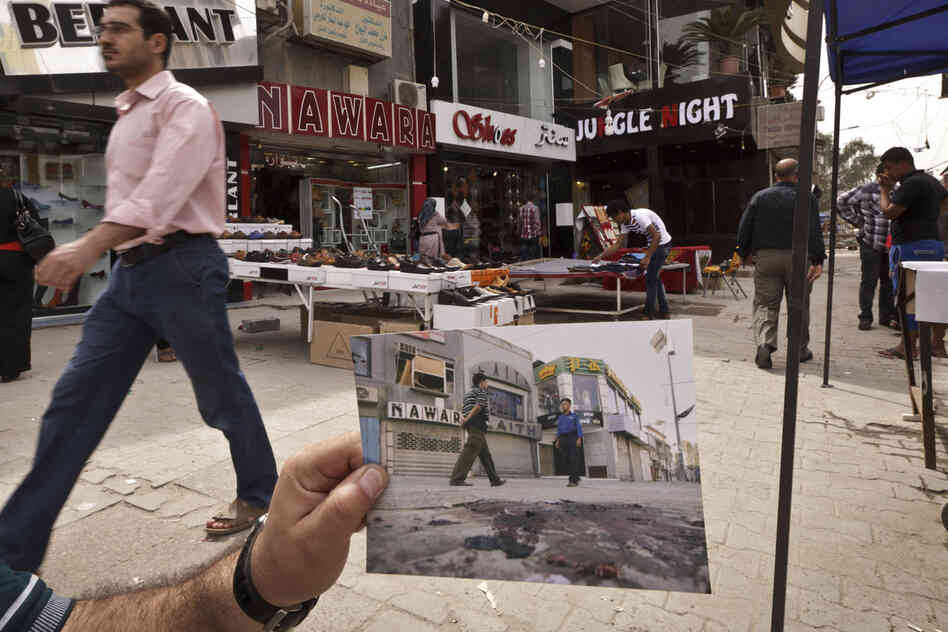 Today, shoppers pass through Baghdad's busy Karrada shopping district. The 2008 photo, taken by Hadi Mizban, shows the scene after a bombing that killed 22 people. Bloody attacks launched by terrorists who thrived in the post-invasion chaos are still frequent, although less so than a few years back.