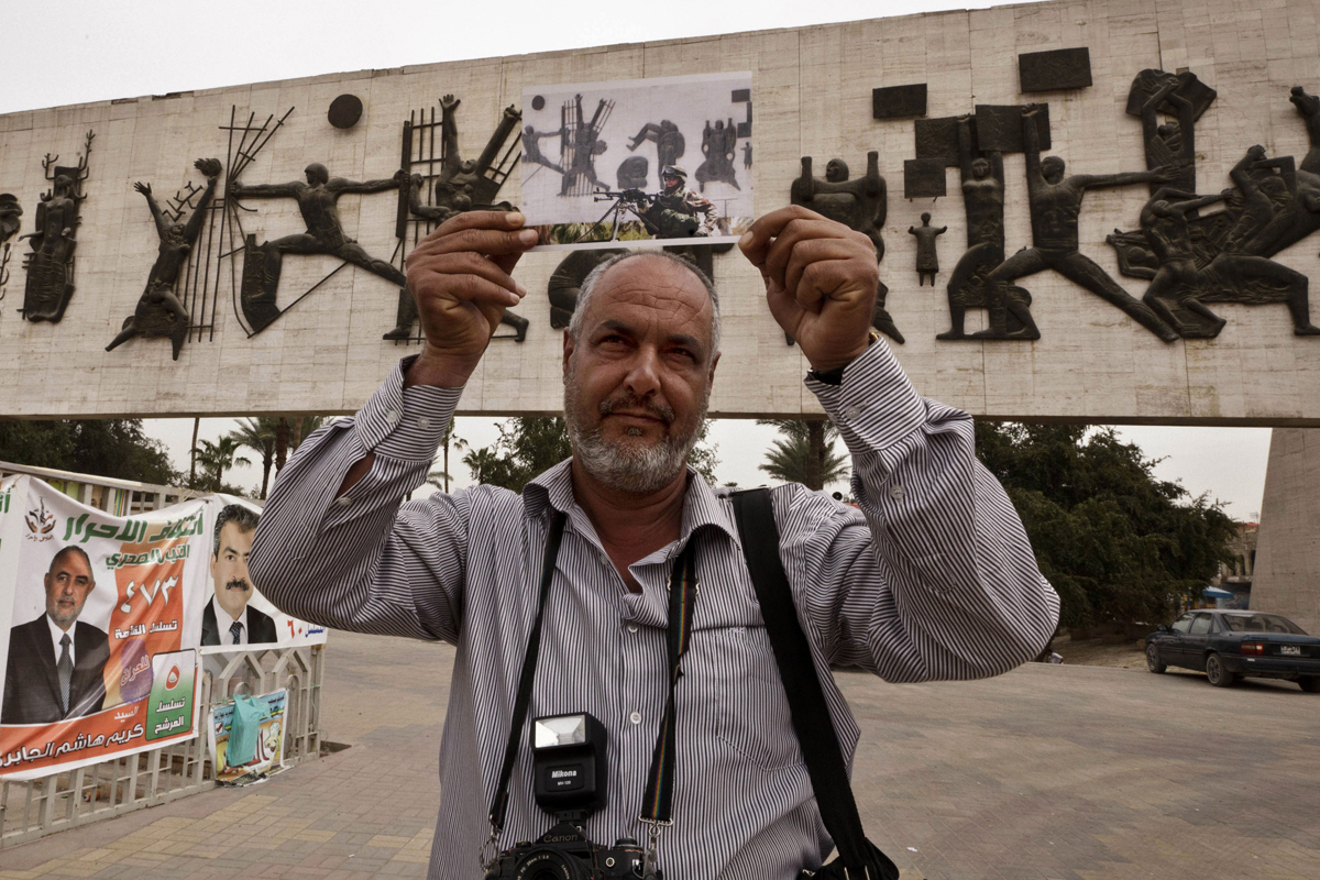 Street photographer Raad Mohammed poses with a photograph taken by photographer Khalid Mohammed in Baghdad's Tahrir Square. The 2006 image shows an Iraqi soldier manning a checkpoint. It was taken after Baghdad was subjected to a vehicle ban -- an effort to prevent reprisal attacks from suicide car bombs after the killing of Abu Musab al-Zarqawi.