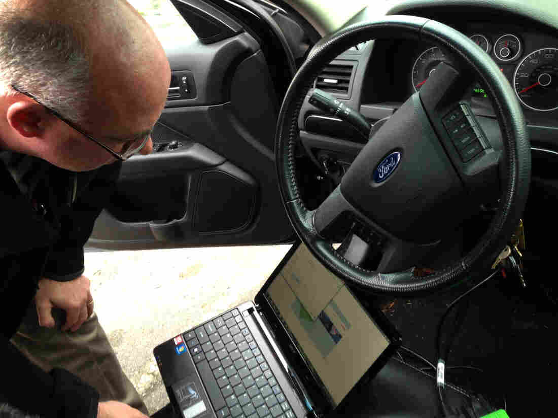Detective Dave Wells plugs his laptop into a car's event data recorder. A large portion of new cars are equipped with the device, and the government is considering m