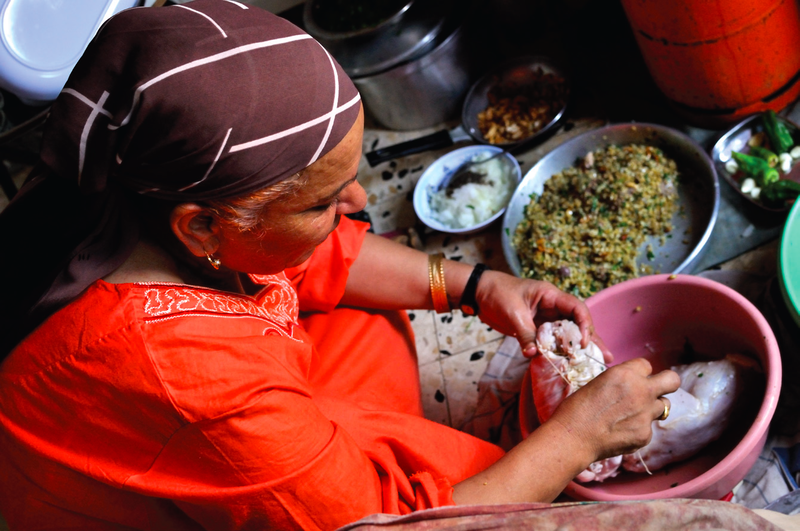 Fatema Qaadan prepares fatta, a meal of buttery rice and griddle bread served with roasted meat.
