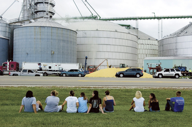 Friends and classmates of Wyatt Whitebread, Alex Pacas and Will Piper watch as rescuers work to free the boys from the bin (center) full of thousands of bushels of corn. Only Piper survived. (AP)