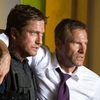 Mike Banning (Gerard Butler) and U.S. President Ben Asher (Aaron Eckhart) flee a destroyed White House in the military-political thriller Olympus Has Fallen.