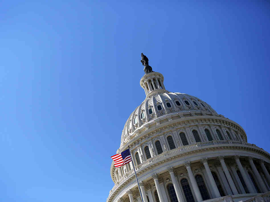 A U.S. flag flies in front of the dome of the U.S. Capitol February 12, 2013.