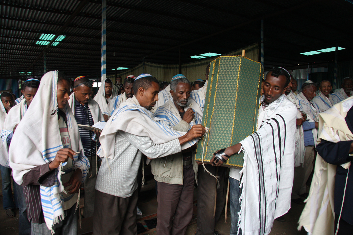 Men at morning prayers touch the Torah Scroll with the fringe of their prayer shawls at a Jewish compound in Gondar, June 2011.