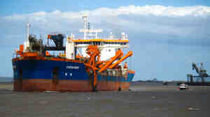 The city of Gladstone near the Great Barrier Reef is the world's fourth largest coal-export hub. Dredges, like one seen here, have turned the harbor brown as they work to expand the coal port.