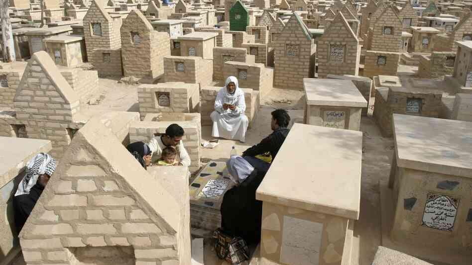 Residents visit the tomb of a  loved one at the New Kerbala cemetery in the holy city of Kerbala, Iraq, in 2007.