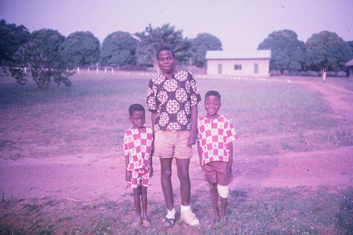 """A man stands with two children. My mother always loved colorful Nigerian cloth, so it's little wonder why she took this photograph."""