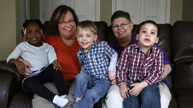 April DeBoer (second from left) sits with her adopted daughter Ryanne (left) and partner, Jayne Rowse (fourth from left), and her adopted sons Jacob (middle) and Nolan (right) at their home in Hazel Park, Mich. The lesbian couple's desire to adopt each other's children has grown into a potentially ground-breaking challenge to Michigan's ban on same-sex marriage. (AP)