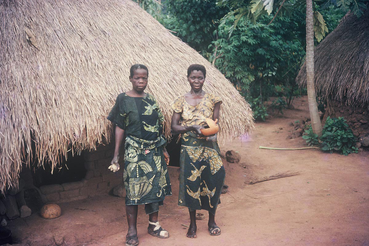 """Two women, most certainly leprosy patients, stand outside their homes. Both of them are wearing a beautiful blue duck-patterned wax-print cloth. The thatch-roof huts were the standard home style in those days. Mud and thatch are still used in rural Nigerian homes, but concrete and tin are favored because they last much longer."""