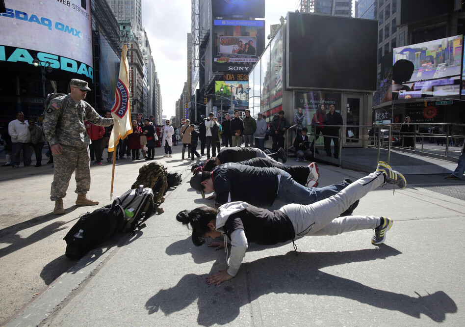 Army recruits perform exercises as part of a demonstration for tourists in front of the military-recruiting station in New York's Times Square.