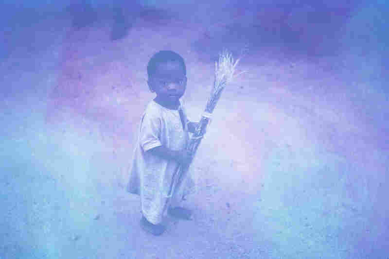 """""""A baby is helping to sweep the yard. The strange color of this photo is due to the poor quality of the slide film, but it does add a strange sense of nostalgia to it. I wonder where this child is now."""""""