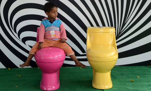 A young boy plays on a commode during an event for World Toilet Day in New Delhi in Novem