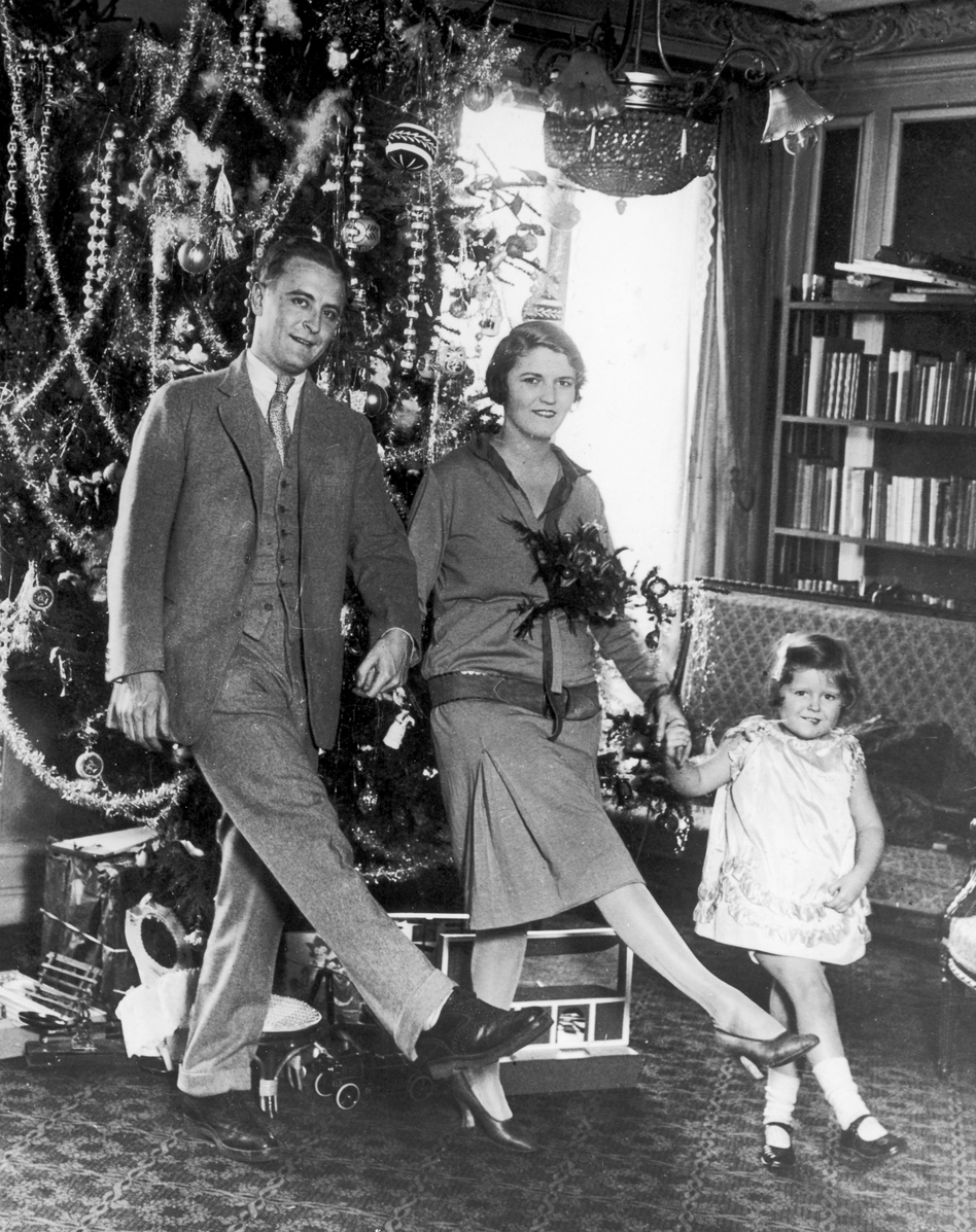 "F. Scott Fitzgerald dances with his wife, Zelda, and daughter, Frances ""Scottie,"" in front of a Christmas tree in Paris. (Getty Images)"