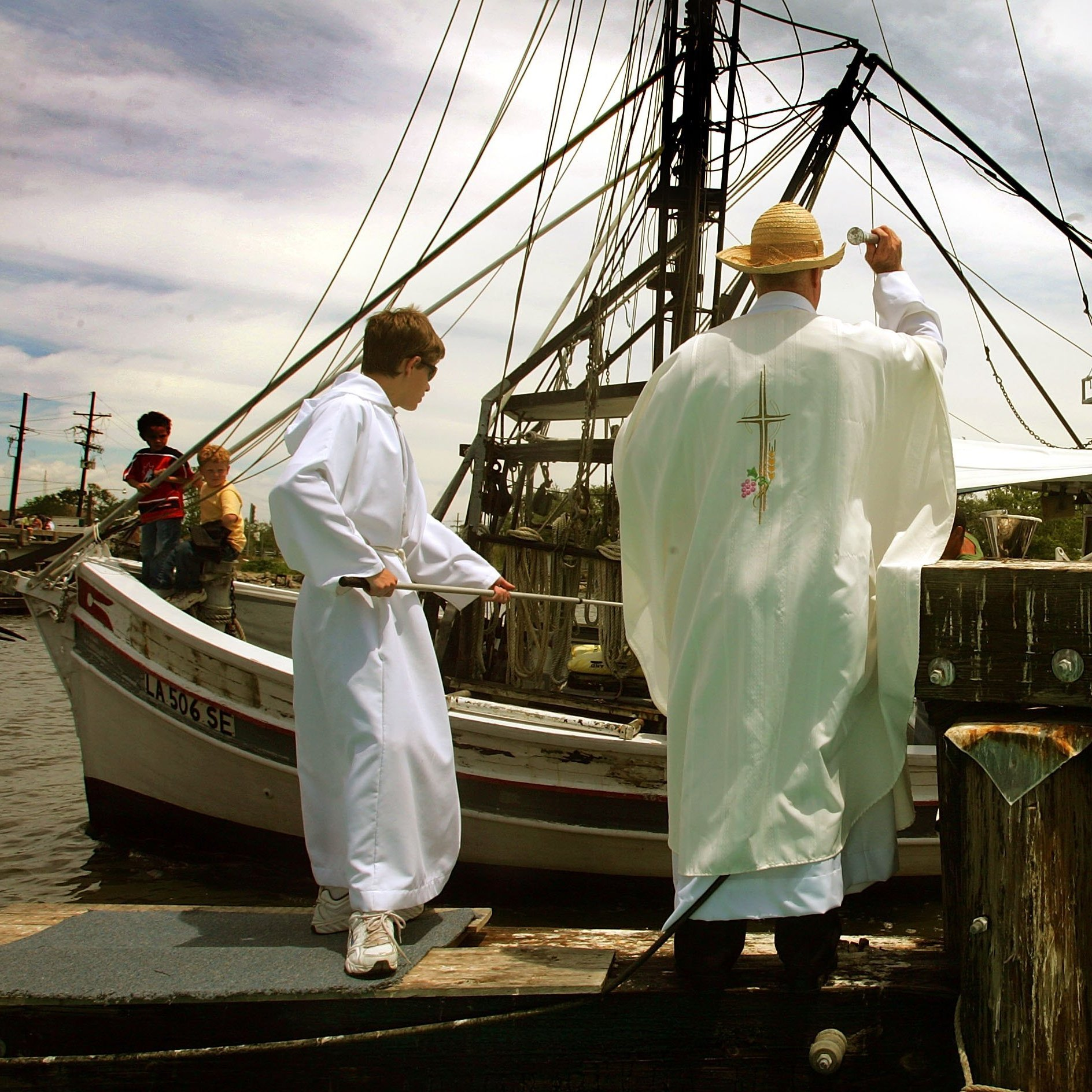 "Father John Ryan of St. Anthony's Catholic Church tosses holy water on a passing shrimp boat as altar servant Samantha Sconza looks on during the annual ""Blessing of the Fleet"" before the start of shrimp season April 30, 2006, in Lafitte, La."