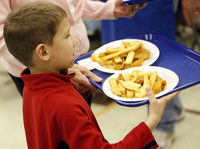A young parishioner carries plates filled with fried fish and potatoes to a table during a Lenten Friday fish fry at St. Frances Cabrini Catholic Church in Littleton, Colo., in 2009.