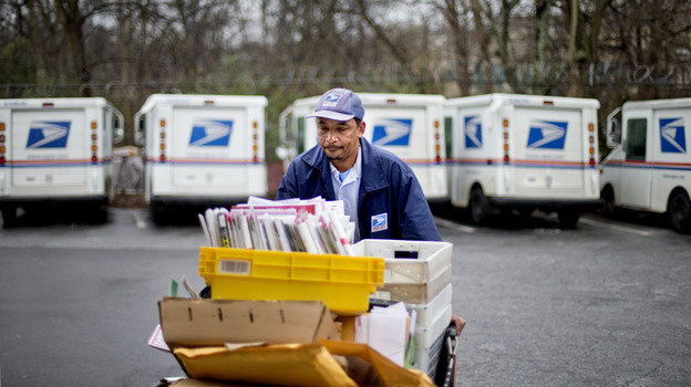 Veteran USPS letter carrier Michael McDonald gathers mail to load into his truck before making his delivery run in the East Atlanta neighborhood on Thursday, Feb. 7, 2013, in Atlanta. (AP)